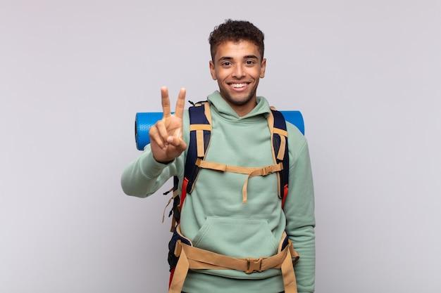 Молодой турист улыбается и выглядит дружелюбно, показывает номер два или секунду рукой вперед, отсчитывая