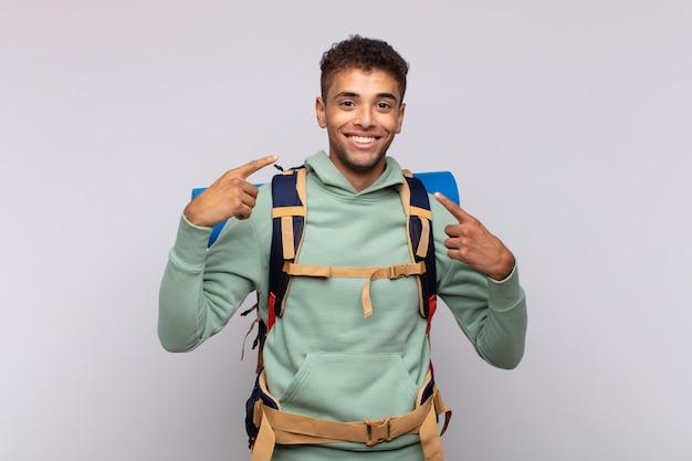 Молодой путешественник уверенно улыбается, указывая на собственную широкую улыбку, позитивное, расслабленное, удовлетворенное отношение