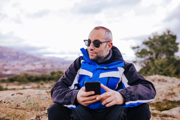 山の上にスマートフォンを使用して若いハイカー男。曇りの日