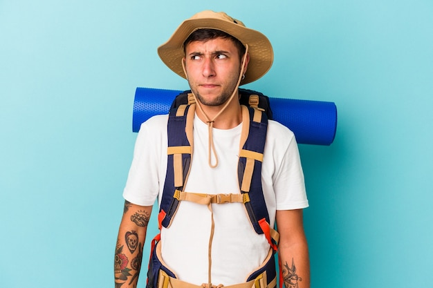 Young hiker man with hat isolated on blue background  confused, feels doubtful and unsure.