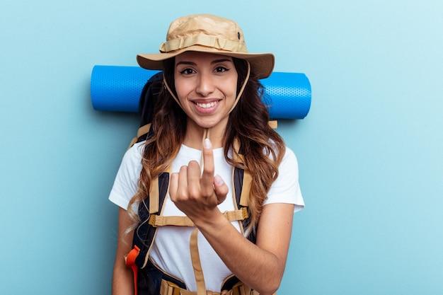 誘うようにあなたに指を指している青い背景に分離された若いハイカー混血の女性が近づいています。