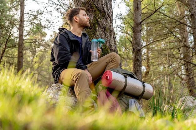 エネルギーを回復する広大な山の森を観察する石の上に座っている若いハイカー、男はキャンプ服と大きなバックパックを身に着けています