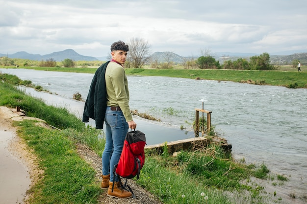 Young hiker standing near flowing river with holding backpack looking at camera