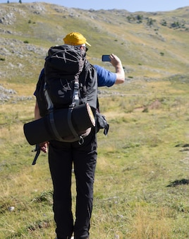 Young hiker with backpack and boots taking smartphone photo