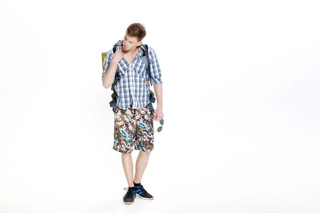 Молодой турист с рюкзаком на белом фоне