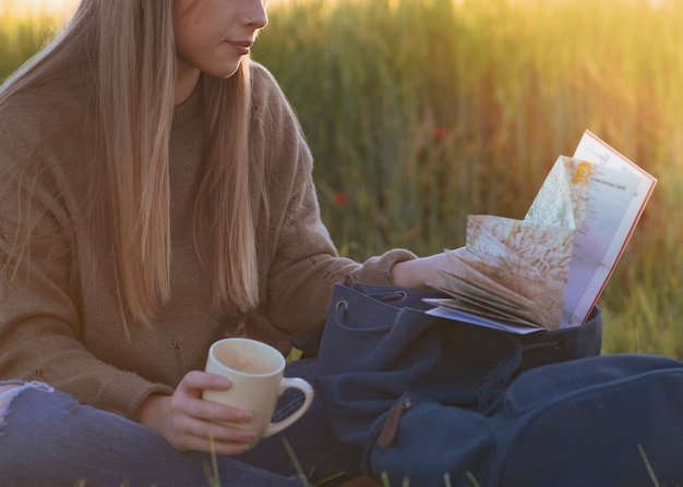 Young hiker woman rests with tea a backpack and a map in the summer nature at sunset. travel concept