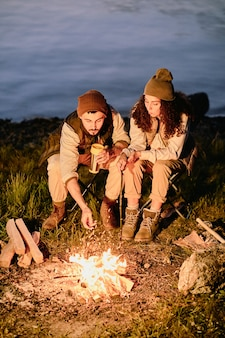 川や湖の背景にキャンプファイヤーのそばに座って、リラックスして揚げマシュマロとお茶やコーヒーを飲む若いハイカー