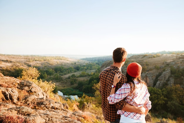 Молодая пара пеших прогулок, глядя на долину