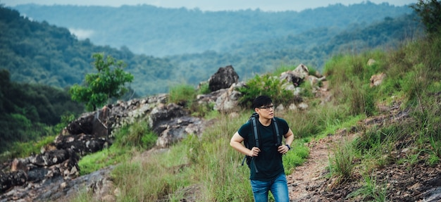 Young hiking man with backpack walking outdoor alone into the wild.