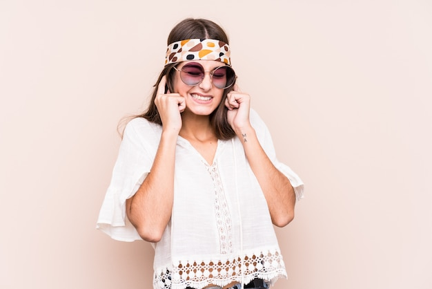 Young hippie caucasian woman covering ears with hands.