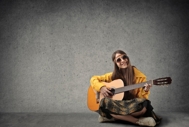 Young hippie girl playing on a guitar