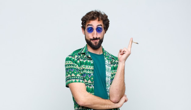 Young hippie man smoking a joint against white wall