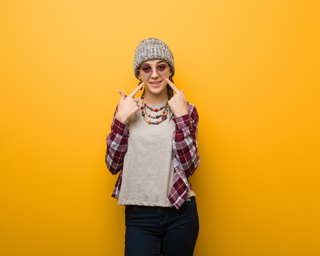 Young hippie natural woman smiles, pointing mouth