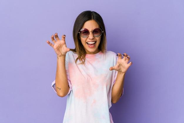 猫を模倣した爪、攻撃的なジェスチャーを示す紫色の背景に分離された若いヒッピーの女性。