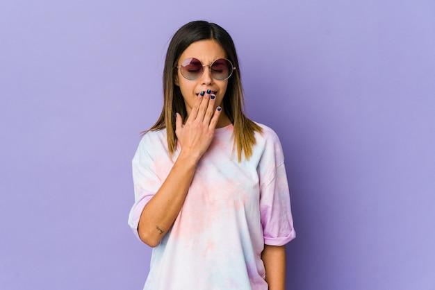 手で口を覆う疲れたジェスチャーを示すあくびをする紫色の背景に分離された若いヒッピーの女性。