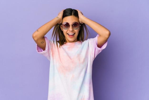 紫色の叫び声で孤立した若いヒッピーの女性は、非常に興奮し、情熱的で、何かに満足しています。