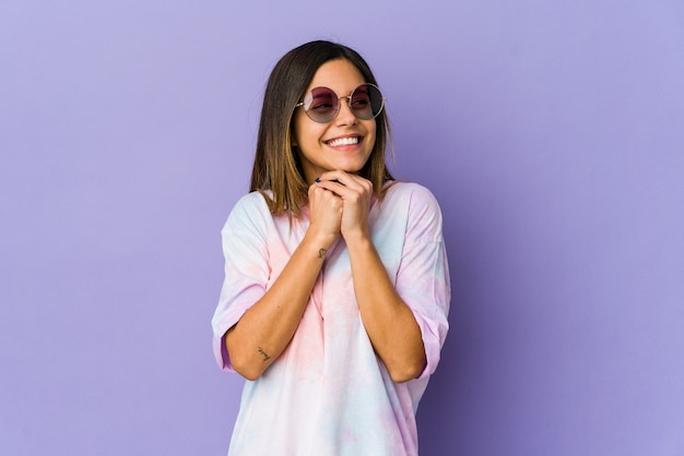 Young hippie woman isolated on purple background keeps hands under chin, is looking happily aside.