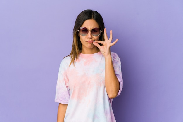 Young hippie woman isolated on purple with fingers on lips keeping a secret.