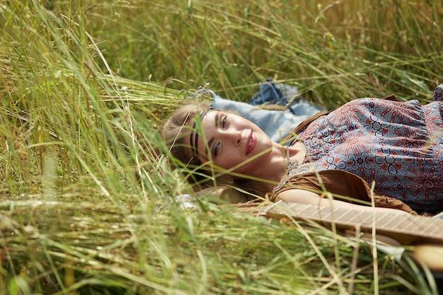 草の上に横たわっている若いヒッピーの女性