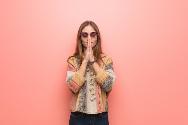 非常に幸せと自信を持って祈るピンクの壁に若いヒッピー女性