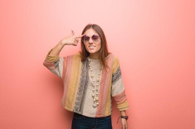 Young hippie woman on pink background doing a disappointment gesture with finger