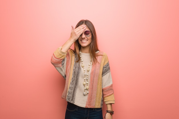 Young hippie woman on pink background forgetful, realize something