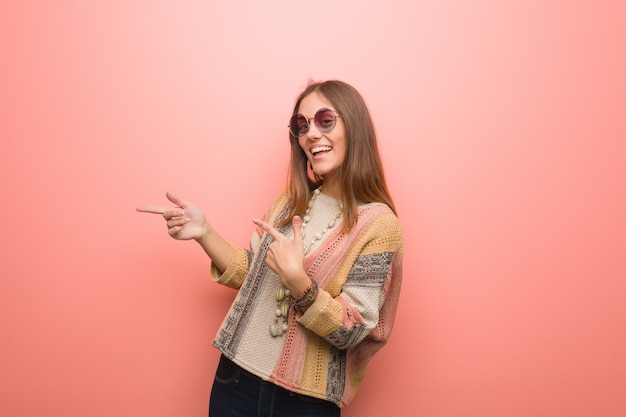Young hippie woman on pink background pointing to the side with finger