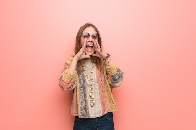 Young hippie woman on pink background shouting something happy to the front