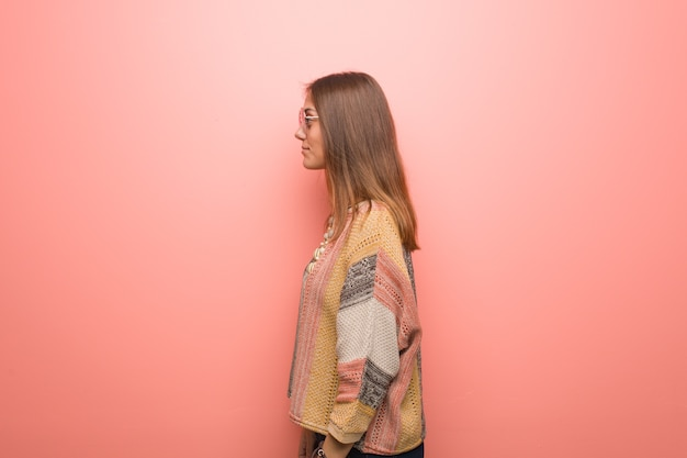 Young hippie woman on pink background on the side looking to front