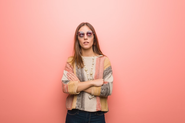 Young hippie woman on pink background tired and bored