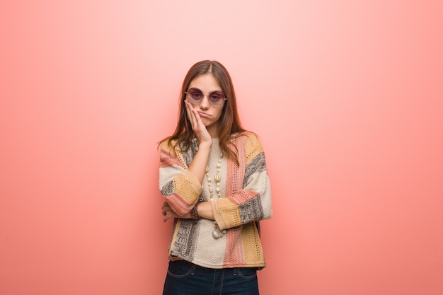 Young hippie woman on pink background tired and very sleepy