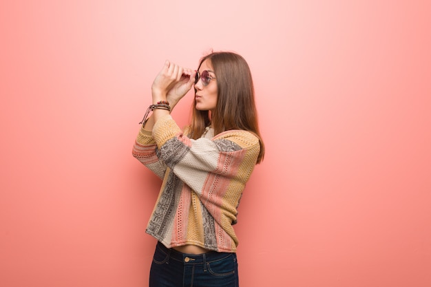 Young hippie woman pink  making gesture of a spyglass