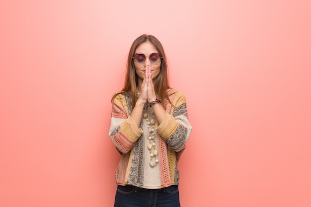 Young hippie woman on pink wall praying very happy and confident