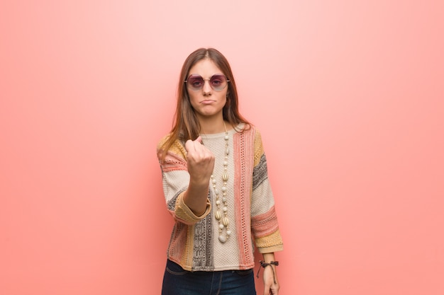 Young hippie woman on pink wall showing fist to front, angry expression