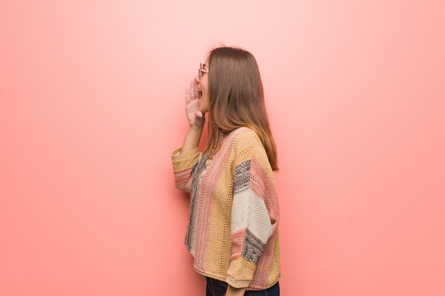 Young hippie woman on pink wall whispering gossip undertone