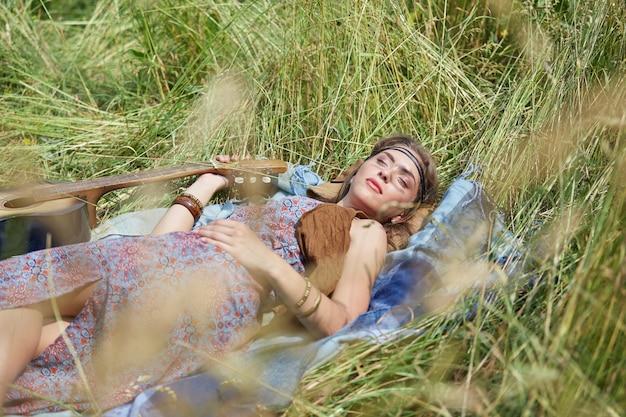 잔디에 누워 편안한 젊은 히피 여자. 복사 공간이 있는 사진.