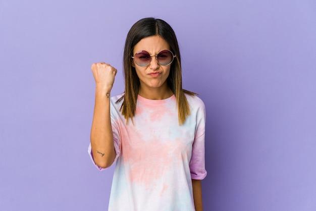 Молодая женщина хиппи показывает кулак, агрессивное выражение лица.