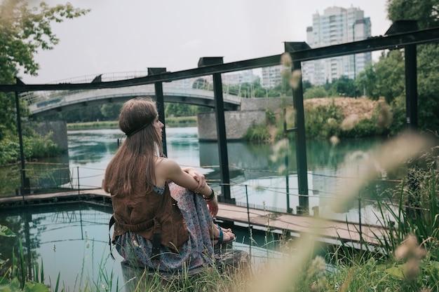 도시 연못 근처에 앉아 젊은 히피 여자. 자연과의 일체감 개념