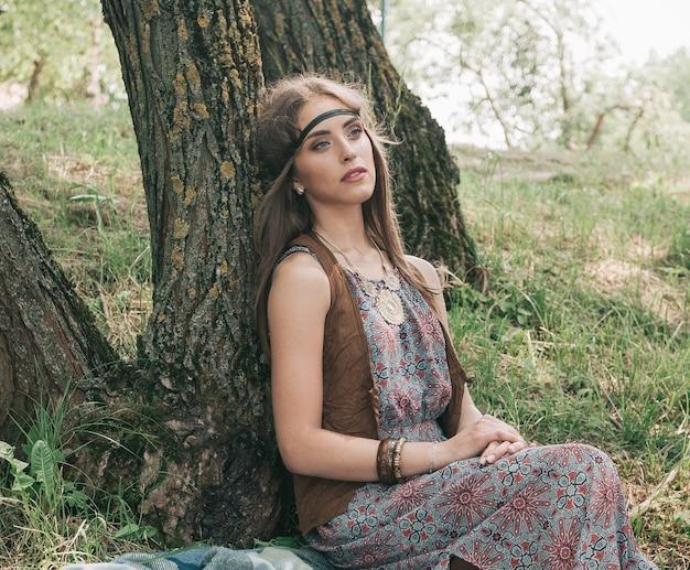 森の木の近くに座っている若いヒッピーの女性