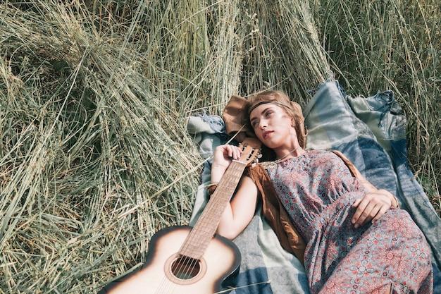깎은 잔디에서 자고 있는 젊은 히피 여자