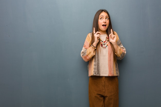 Young hippie woman surprised pointing up to show something