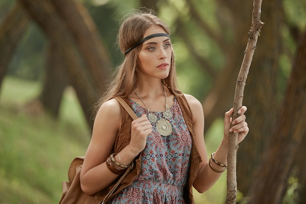 Young hippie woman with a bag walking through the woods