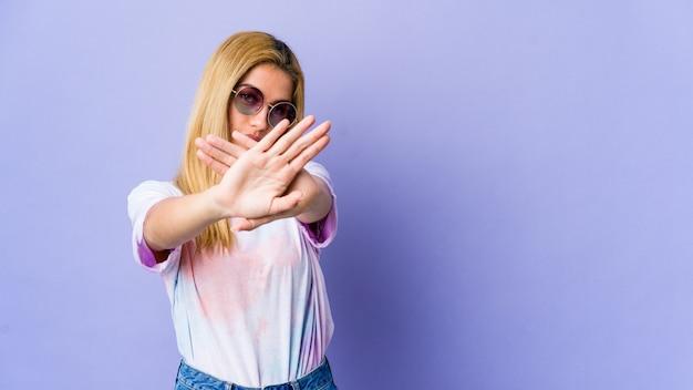Молодая хиппи женщина в очках делает жест отрицания