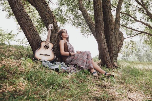 森の木の近くに座っているギターと若いヒッピーの女性