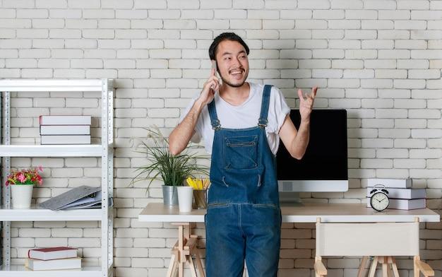 立っている若い流行に敏感なひげアジア人男性は、彼の新しいモダンなミニマルスタートアップオフィスで幸せにスマートフォンで電話をかけることができます。
