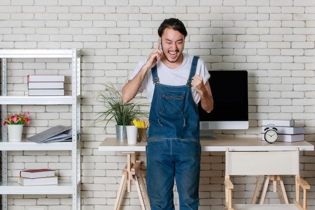 立っている若い流行に敏感なひげアジア人男性は彼の新しい現代で幸せにスマートフォンで電話をかけることができます