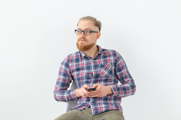 Молодой хипстерский бородатый мужчина, сидящий над белой стеной с копией пространства