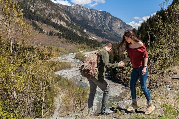 流行に敏感な若い美しいカップルの森の川でハイキング