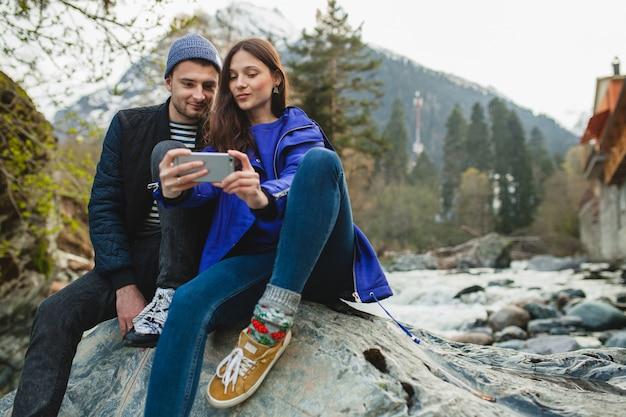 スマートフォンを押し、写真を撮って、冬の森の川の岩の上に座って恋に流行に敏感な若い美しいカップル