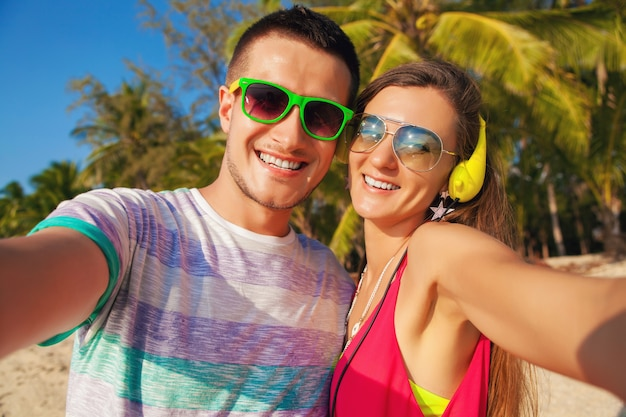 Молодая хипстерская красивая влюбленная пара, делающая селфи-фото на тропическом пляже, летние каникулы, счастливы вместе, медовый месяц, красочный стиль, солнцезащитные очки, наушники, улыбка, счастливая, веселая, позитивная